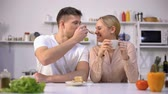 nourishment : Young man pretending to feed girl with cake, couple having fun in kitchen. Stock Footage