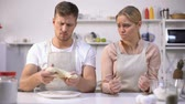 sticky : Clumsy man stretching dough, looking at wife, couple has difficulty making cake Stock Footage