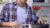 cookery : Man cooking breakfast, adding ground pepper into frying pan, seasoning dish Stock Footage