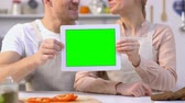 hombres : Smiling family couple in aprons showing green screen tablet at camera. Archivo de Video