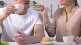 hombres : Cute girlfriend feeding beloved man with sweet homemade cake, drinking coffee