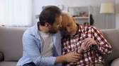 rozvod : Middle-aged son comforting retiree terminally ill father, suffering pain, care