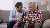 относительный : Adult father and son relaxing on weekend drinking beer and talking, togetherness Стоковые видеозаписи