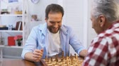 satranç : Adult males playing chess, father and son competing, hobby and leisure activity Stok Video