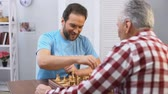 шах и мат : Middle aged male volunteer playing chess with elderly man in nursing home, hobby