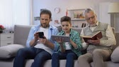 parentes : Middle-aged male and preteen boy scrolling gadgets, aging man reading paper book