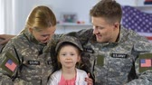 serviceman : Male and female soldiers hugging daughter in military cap, smiling on camera
