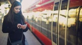 pendulares : Attractive lady standing near train and typing on smartphone, online tickets