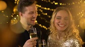 yıldönümü : Celebrating young couple toasting drinking champagne, festive lights background Stok Video