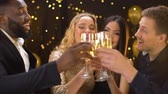 clinking : Multi-racial group of friends clinking glasses of champagne, smiling on camera Stock Footage
