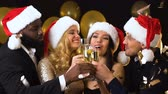 clinking : Happy multiracial friends in santa hats clinking champagne, New Year party