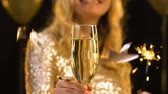 Бенгалия : Smiling blond lady holding glass of champagne and bengal light, confetti falling