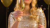 Бенгалия : Smiling woman in gold dress enjoying party with champagne and bengal light