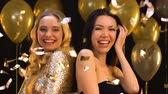 multirracial : Happy multiracial women smiling and having fun at party under falling confetti Stock Footage