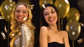 flört etme : Multiracial female friends smiling and flirting under falling confetti, party