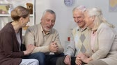 nyugdíj : Two senior couples talking and laughing in nursing home, friends communication Stock mozgókép