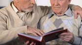 fotky : Two male friends looking photo album hugging, old time memories, nostalgia Dostupné videozáznamy