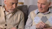 doação : Two retired men counting coins in hands, pension poverty, financial crisis Stock Footage
