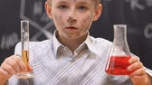 bűnösség : Confused schoolboy shrugging shoulders, dirty face after chemical experiment
