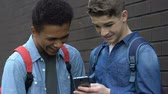 kurban : Multiethnic teens scrolling phone and laughing forbidden content lack of control