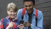 kurban : Disrespectful multiracial guys scrolling smartphone and laughing, mocking