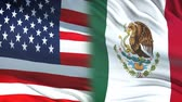 archief : USA and Mexica officials exchanging confidential envelope, flags background