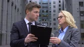 colega de trabalho : Male company worker discussing contract details with mature female colleague Stock Footage