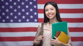 uitspraak : Cheerful Asian girl smiling with books against USA flag background, education