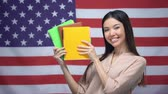 słownik : Asian girl smiling against USA flag background, student holding copybooks Wideo