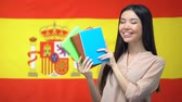 uitspraak : Asian girl showing copybooks against Spanish flag background, learning language
