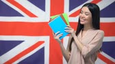 uitspraak : Pretty female student showing copybooks against British flag, learning language Stockvideo