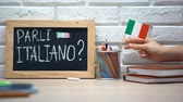 uitspraak : Do you speak Italian written on board, hand putting Italy flag in box, language