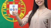 vlag portugal : Joyful female showing thumbs up closeup Portuguese flag background, visa service Stockvideo