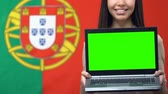 portugália : Laptop with green screen in female hands, Portugal flag background traveling app