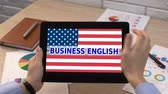 dilbilgisi : Business English application against USA flag on tablet in female hand, tutorial Stok Video