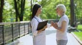 assistent : Young nurse talking with elderly woman at rehabilitation center park, healthcare