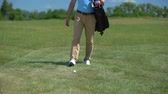 удара : Man golfer putting sport equipment bag on green, taking club and ready to play