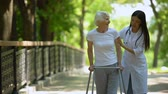 rehabilitasyon : Female doctor helping elderly woman with walking frame, hospital park, outdoors