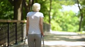 tag : Elderly woman moving with walking frame at rehabilitation center park, back view