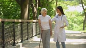 enfermagem : Doctor walking in park with elderly female patient with cane, rehabilitation Stock Footage
