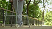 rehabilitasyon : Legs of patient slowly moving with help of walking frame in hospital park Stok Video