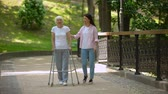 rehabilitasyon : Granddaughter supporting disabled grandma with walking frame, day in park