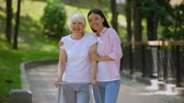 rehabilitasyon : Young female hugging elderly woman with walking frame outdoors, rehabilitation