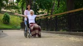 rehabilitasyon : Happy volunteer pushing wheelchair with positive old lady, joyful female patient