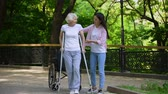 rehabilitasyon : Young woman helping old lady walking on crutches, hip fracture rehabilitation