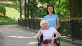 enfermagem : Smiling female volunteer and disabled senior woman looking camera, charity