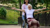 rehabilitasyon : Smiling volunteer in park with inspired old woman in wheelchair raising hands Stok Video