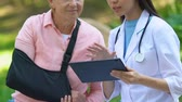 honda : Doctor using tablet pc explaining examination result to old female in arm sling Archivo de Video