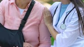 omuz : Female therapist supporting old woman in arm sling outdoors, rehabilitation Stok Video