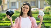 trio : Cute female showing camera and bunch of dollars at camera, profitable profession Stock Footage